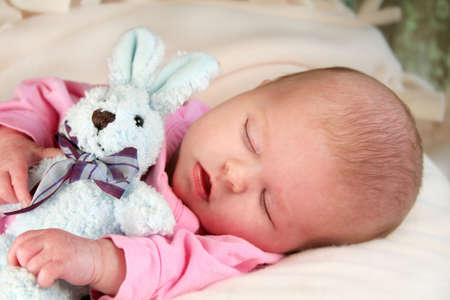 Infant baby girl sleeping with a bunny rabbit. Stock Photo