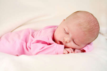 Cute baby girl sleeping with her hands under her face, laying on a white blanket. Stock Photo