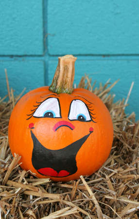 Smiling pumpkin with a painted face and sitting on hay with a blue background. Stock Photo