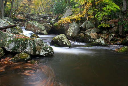 soften:   A secluded cascade in the forests of Virginia during Fall of the year. Taken with a slow shutter speed to smooth and soften the water.  Stock Photo