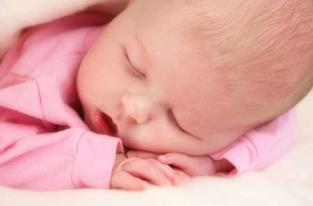 Close up of a baby girl sleeping with her hands under her face.   Stock Photo