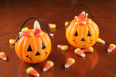 Small plastic pumpkins holding candy corn with some laying on a table top.