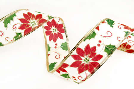 Christmas ribbon with holly and Poinsettias against a white background.