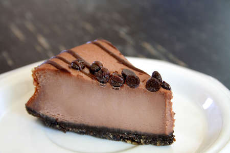 cheesecake: Delicious chocolate cheese cake with chocolate chips on a white plate. Stock Photo
