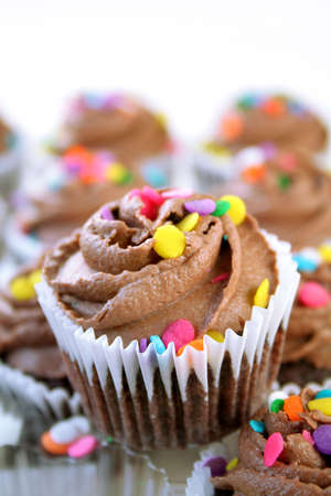 Chocolate cupcakes with colorful sprinkles shot with a shallow DOF and selective focus. Room for text.