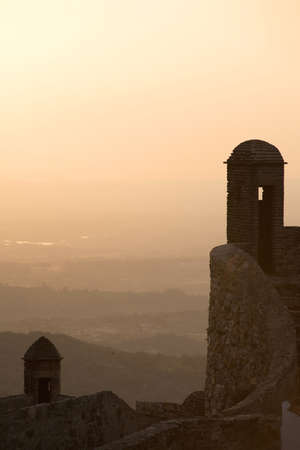 turrets: Turrets on the castle of Marvao stand in silhouette over the Alentejo countryside at sunset. Marvao, Portugal. July 17, 2015.
