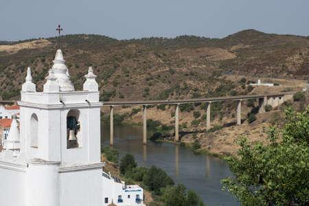 The steeple of the main church Igreja Matriz of Mertola and the bridge that crosses the Guadiana River