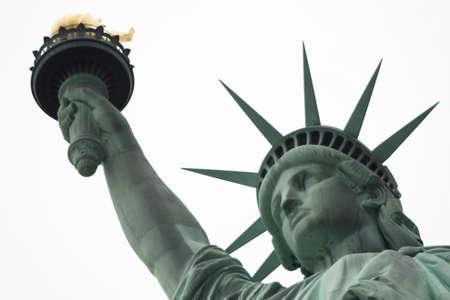 lady liberty: Cerca de la Estatua de la Libertad cabeza, los brazos y de las llamas en un cielo de fondo blanco Foto de archivo