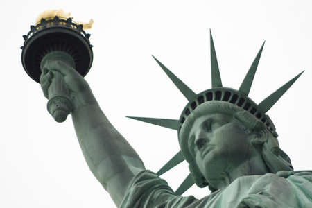 Close up of the Statue of Liberty head, arm and flame on a white sky background photo