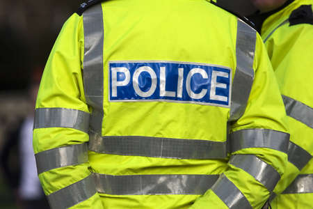 yellow jacket: Shot of the back of a police officers jacket with the word police written across the back Stock Photo