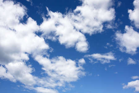 White fluffy Cumulus clouds on a blue sky background photo