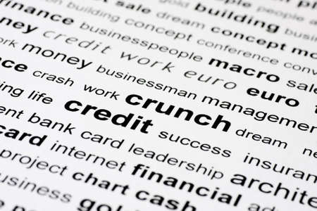 words credit and crunch in black on white background with other financial key words out of focus photo