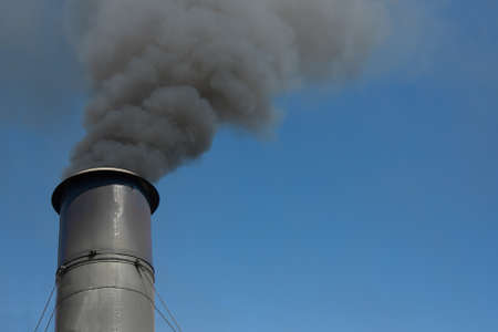 smoke stack: Close up of a metal smoke stack spewing out thick black smoke into a perfect blue sky.