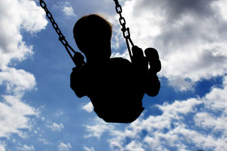swinging: Silloutte of a young child swinging high with a blue sky and white clouds in the background. Stock Photo