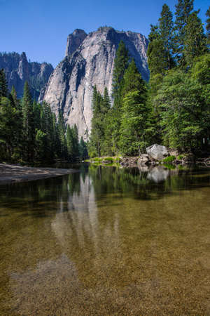 granite park: image of yosemite national park with a large granite cliff surrounded by trees and a river at the bottom of the image Stock Photo