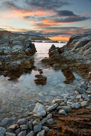kaikoura: HDR photo of sea, rocks and sunrise sky with clouds in Kaikoura, New Zealand.