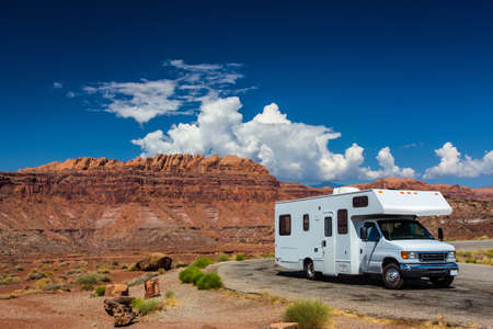 white RV  campervan in canyonlands USA with red cliffs and blue sky behind it