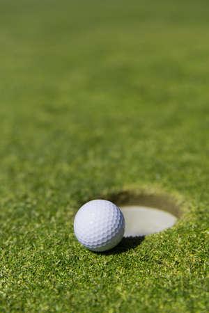 Golf ball: cerca de una pelota de golf blanca en el borde de un agujero con un indicador