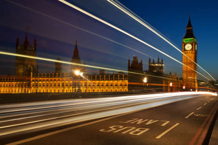 government: Light trails from London buses and vehicles with the Elizabeth Tower  Big Ben  of the Palace of Westminster in the background and the words Bus Lane in the foreground Stock Photo