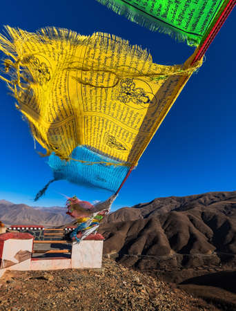 Tibetan prayer flags outstreached in the wind at a high roadside mountain pass with a blue sky and mountains in the distance 스톡 콘텐츠
