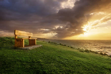 A bench on a seaside cliff with a dramatic sunrise loooking out over the ocean as the storm clouds clear. Reklamní fotografie