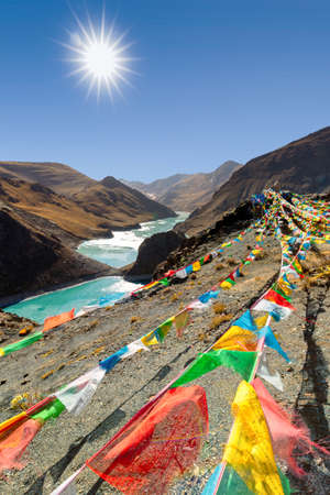 Tibetan prayer flags flying in the wind of a mountain pass in the himalyas with a blue sky and dramatic view. 스톡 콘텐츠