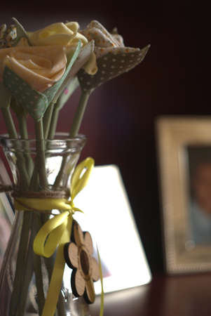 Silk flower gift in a glass vase sit on a sideboard with defocussed photoframes in background Stockfoto