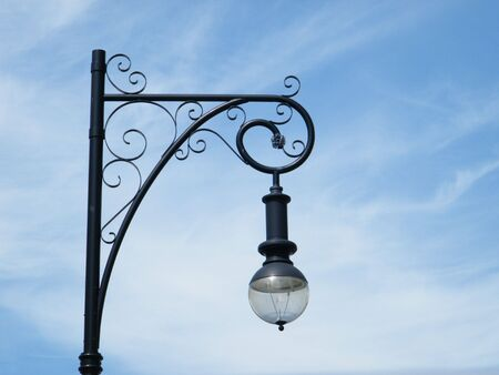 lamp post: Isolated ornate street light against a blue sky background