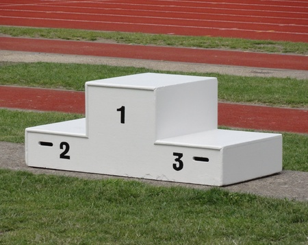 winners podium: isolated sporting podium with athletics track in the background Stock Photo
