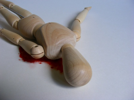 stabbed: Photo Illustration of the death of a wooden figure