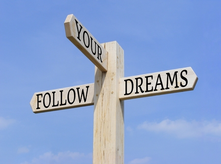 crossroads sign: Signpost with the words \Follow Your Dreams\ over a blue sky background