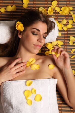 Woman relaxing in health spa with yellow rose petals photo