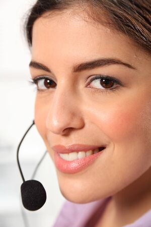 Close up young female receptionist talking on headset photo