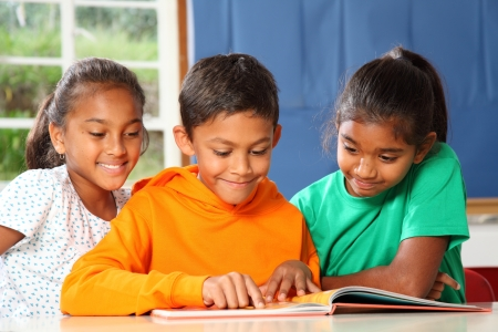 kids reading book: Primary school children in class reading learning