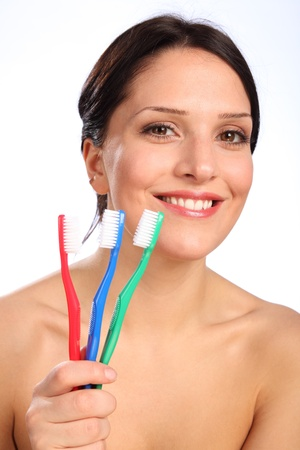 Beautiful smiling young woman posing with three colourful toothbrushes against a white background, promoting healthy oral hygiene. photo