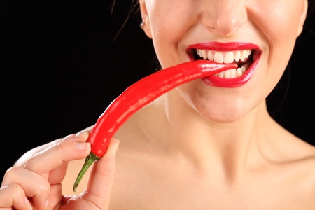 Close up beauty shot of womans mouth with bright red lipstick as she bites onto a chili pepper photo