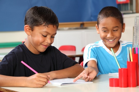nine years old: Two happy school boys sharing learning in class Stock Photo