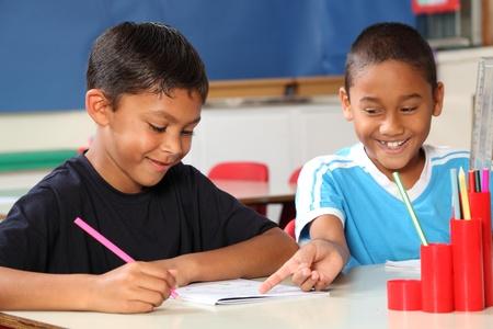 Two happy school boys sharing learning in class Фото со стока
