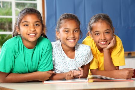 child classroom: Three happy school girls reading a book in class