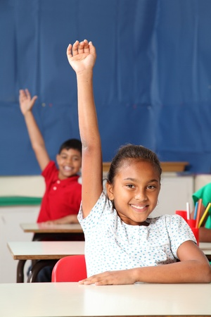 school work: Two smiling young school children arms raised in class