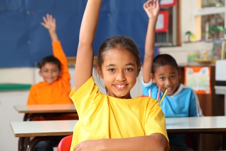students in classroom: Three primary school children hands raised in class