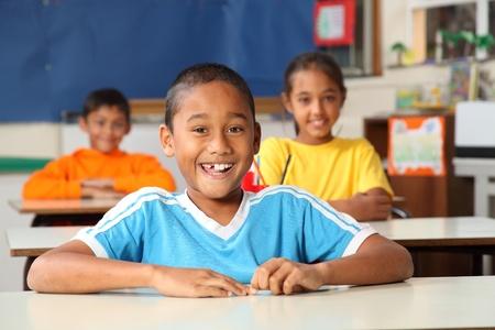ni�os en la escuela: Ni�os de primaria alegre en el aula Foto de archivo