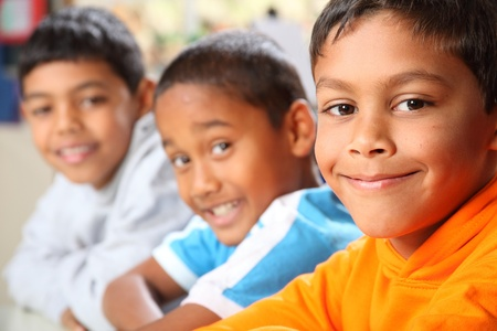 child learning: Row of three smiling young school boys in class Stock Photo