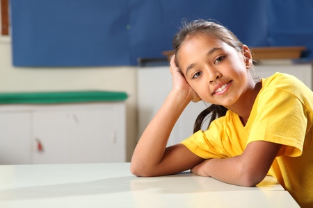 School girl age ten relaxed while sitting at her classroom desk Stock Photo - 9509839