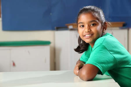one child: Smiling school girl at class desk