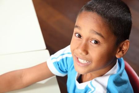 garçon ecole: Souriante jeune �colier 9 � son bureau en classe