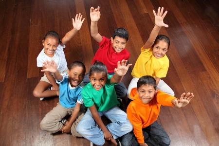 classroom: Six school children sitting in classroom hands up