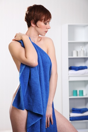 Beautiful woman drying of with towel from the shower Фото со стока
