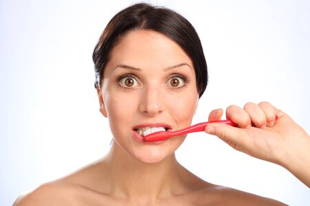 Fun shot on white background of beautiful young woman cleaning her teeth with large eyes wide open. photo