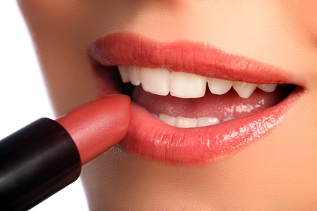 red lipstick: Close up beauty shot of woman applying lipstick to lips with mouth open. Image has been retouched.